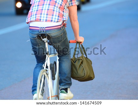 Person on bike seen from behind. - stock photo