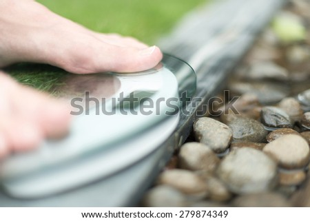 Person on scale with only feet to be seen on green lawn and wet pebble background. Person measures weight in spa setting. Health care and weight loss. Spa helps to be fit. - stock photo