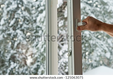 person opens a window with a mosquito net - stock photo