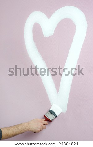 person paints a heart on a pink wall