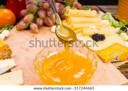 Person pouring delicious golden honey from a spoon into a bowl on a buffet table surrounded by a large assortment of different gourmet cheeses with a bunch of fresh grapes - stock photo