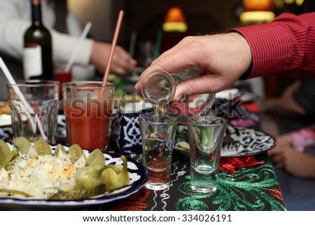 Person pouring vodka in the uzbek restaurant - stock photo