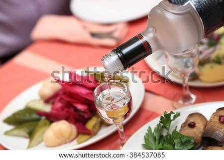Person pouring vodka into glasses in the restaurant - stock photo