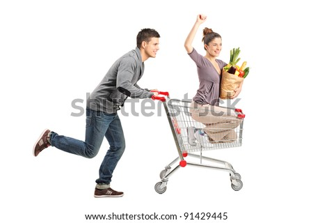 Person pushing a happy woman in a shopping cart with paper bag ful with food isolated on white background - stock photo