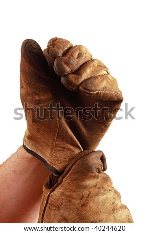 Person puts on a pair of worn work gloves, isolated on a white background. - stock photo