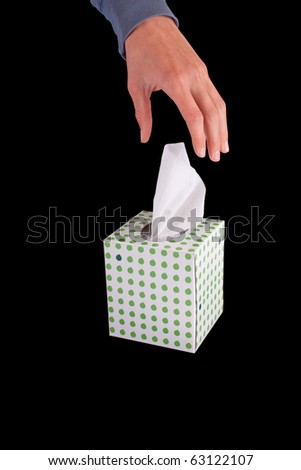 person reaches for tissue to blow runny nose with, isolated on black