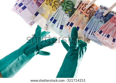 Person reaching for Euro notes on clothesline, close-up - stock photo