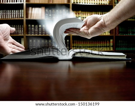 Person reading book in library and flipping pages                      - stock photo
