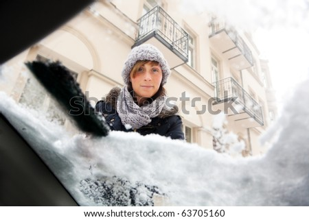 person removing snow and ice from window - stock photo