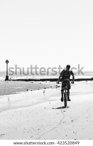 Person riding a bicycle on the beach on hard packed sand next to the water. Viewed from behind. Black and white. High key image. Copy space. - stock photo