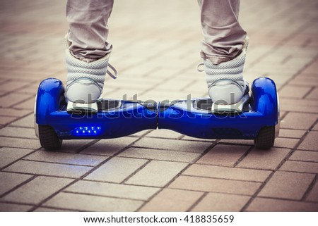 Person riding a modern blue electric mini segway or hover board scooterin outdoors. Popular new city transport that is easy and fun to ride and makes no air pollution to the atmosphere  - stock photo