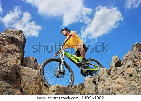 Person riding a mountain bike amid rocks on a sunny day against a blue sky and clouds, low angle view - stock photo
