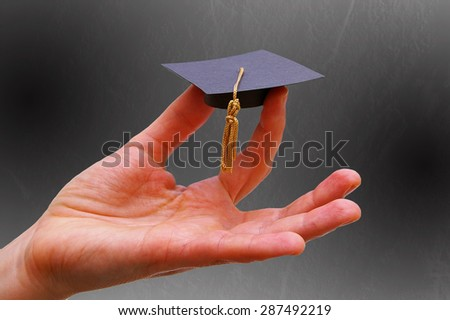 Person's hand holding a miniature graduation cap -- Education or career concept - stock photo