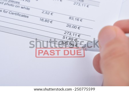 Person's Hand Holding Pen Over Past Due Statement - stock photo