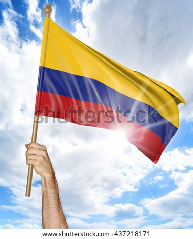 Person's hand holding the Colombian national flag and waving it in the sky, part 3D rendering - stock photo