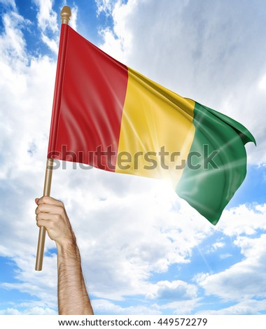 Person's hand holding the Guinean national flag and waving it in the sky, 3D rendering - stock photo