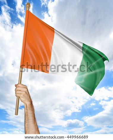 Person's hand holding the Ivory Coast national flag and waving it in the sky, 3D rendering - stock photo
