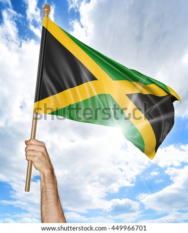 Person's hand holding the Jamaican national flag and waving it in the sky, 3D rendering - stock photo
