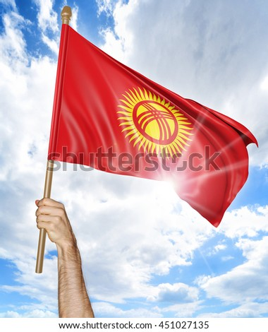Person's hand holding the Kyrgyzstan national flag and waving it in the sky, 3D rendering - stock photo