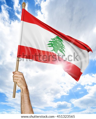 Person's hand holding the Lebanese national flag and waving it in the sky, 3D rendering - stock photo