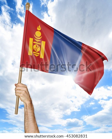 Person's hand holding the Mongolian national flag and waving it in the sky, 3D rendering - stock photo
