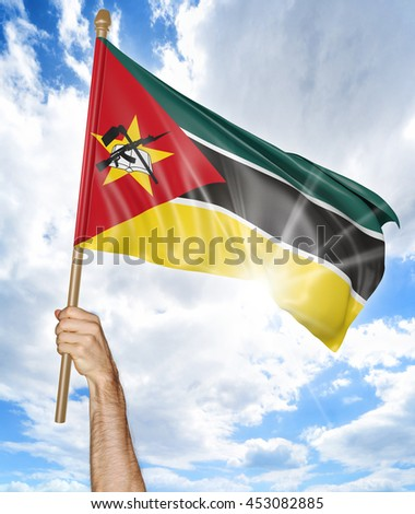 Person's hand holding the Mozambican national flag and waving it in the sky, 3D rendering - stock photo