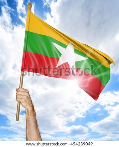 Person's hand holding the Myanmar national flag and waving it in the sky, 3D rendering - stock photo