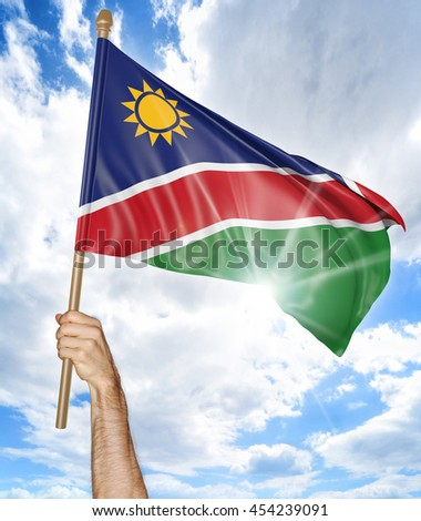 Person's hand holding the Namibian national flag and waving it in the sky, 3D rendering - stock photo