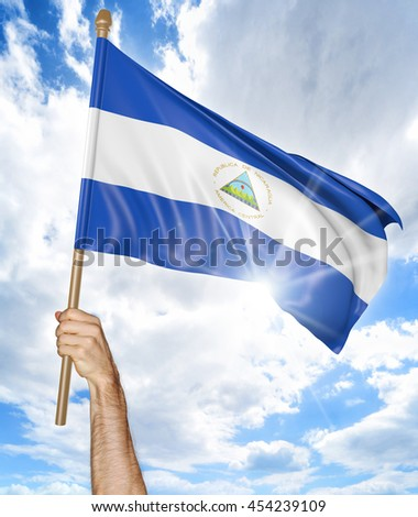 Person's hand holding the Nicaragua national flag and waving it in the sky, 3D rendering - stock photo