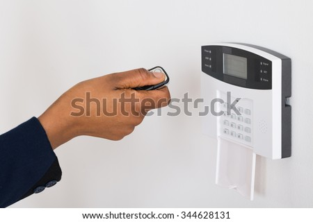 Person's Hand Operating Entrance Security System With Remote In Office