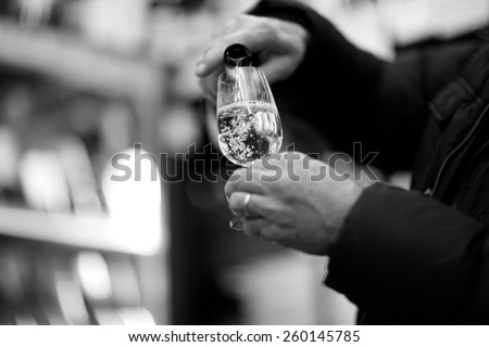 Person's hands pouring bubbly champagne into a glass, monochrome - stock photo
