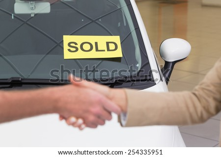 Person shaking hands in front of a sold car at new car showroom - stock photo
