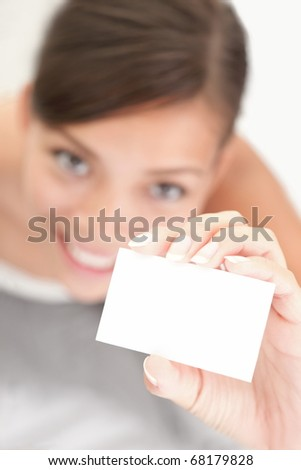 Person showing business card. Casual woman smiling holding the card. Shallow depth of field, focus on paper with empty copy space. - stock photo