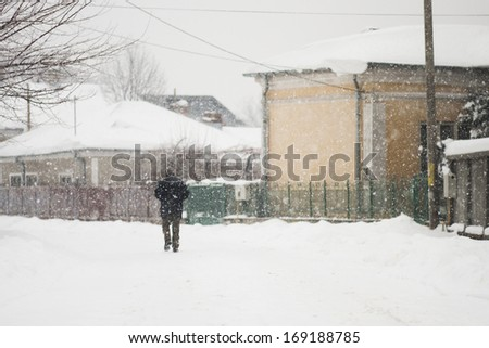 Person silhouette in the street while snowing