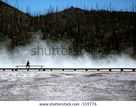 Person silhouetted against mist of Grand Prismatic Hot Spring in Yellowstone National Park, Wyoming - stock photo
