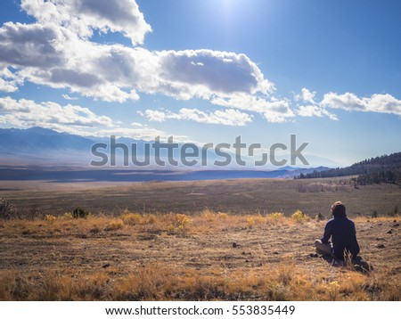 Person sitting on mountain, overlooking valley