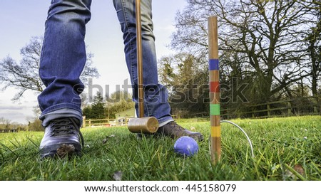 Person standing and playing croquet on grass - stock photo