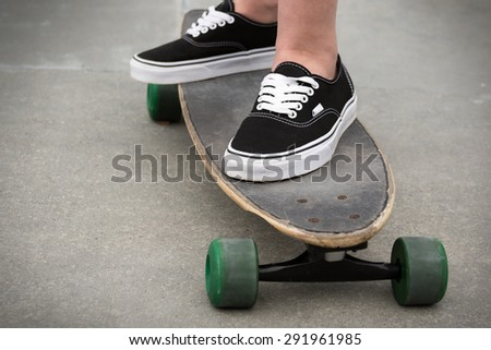 Person standing on a skateboard - stock photo