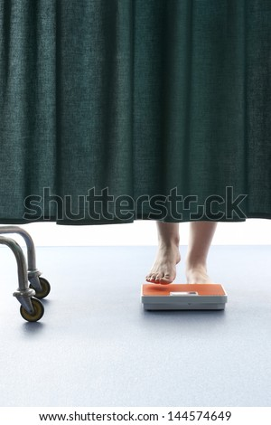 Person stepping onto weighing scales behind curtain in hospital - stock photo