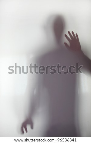 Person stood behind frosted glass - stock photo