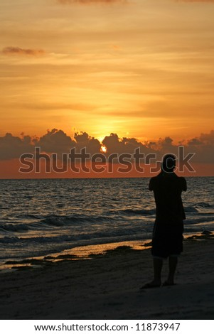 Person taking a picture of sunset in Madeira Beach Florida - stock photo