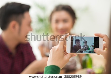 Person taking photo of young couple at party, focus on screen