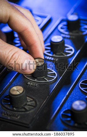 person turning a dial on a mixing board - stock photo