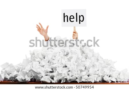 Person under crumpled pile of papers with hand holding a help sign isolated against a white background. - stock photo