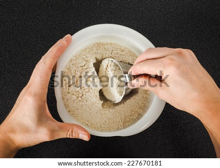 Person using a measurement tool in a bowl of wheat flour - stock photo