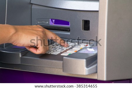 Person Using Keypad Atm Machine To Withdraw Money