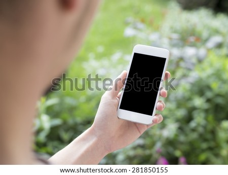 Person using mobile smartphone in white color, Shot with third-person view. Similar to iphon 6 - stock photo