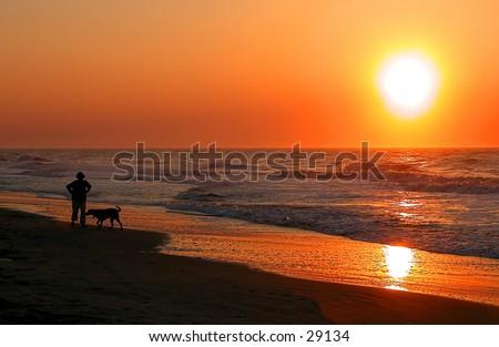 Person walking a dog at sunrise along the South Carolina coast - stock photo