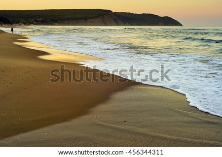 Person Walking in the distance on wild sandy beach under the golden light of a summer evening.                               - stock photo