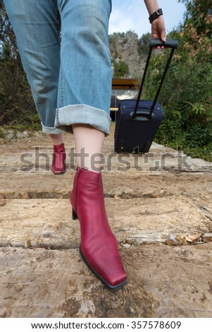 Person walking on old wooden bridge pulling Travel Suitcase female Legs and Hand casual vacation Clothing red attractive high Heels Shoes close up and Jeans green Forest and Mountains on background